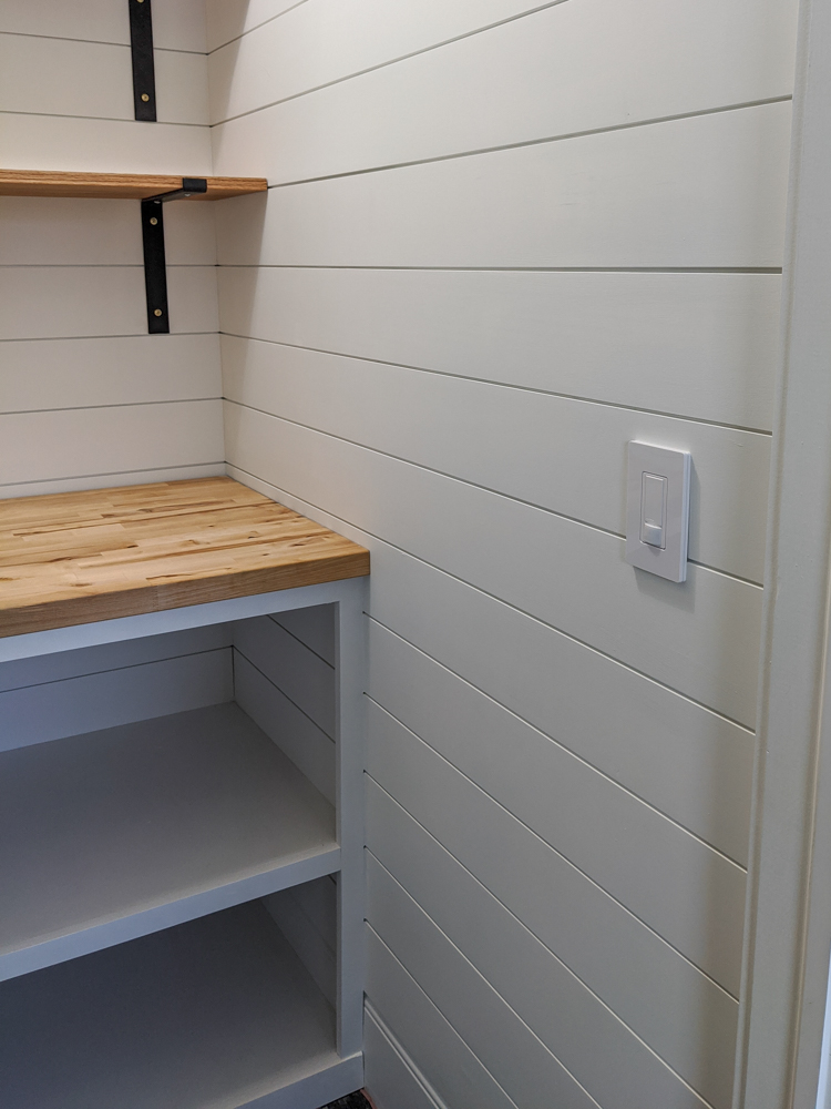 The wood tones and black brackets against the white shiplap really give that classic farmhouse feel to this little pantry space. Click to see more of our farmhouse pantry update.