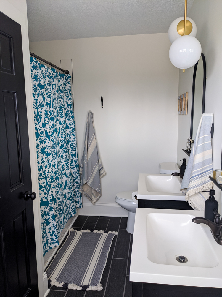 We gave our guest bathroom a quarantine facelift with a mostly black and white color scheme and pops of blue—including this super fun shower curtain. Click to see more.