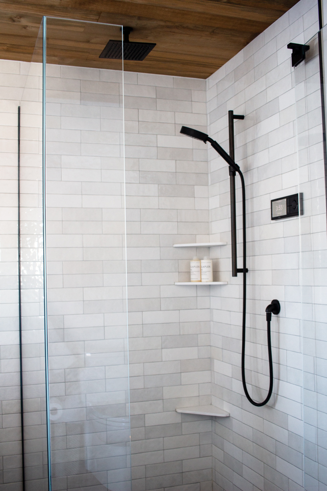 A unique pattern in our white tile, a teak ceiling, and a smart shower—oh my! All of those elements combine into one sexy shower. Click to see the rest of our black and white bathroom and shop every single source.