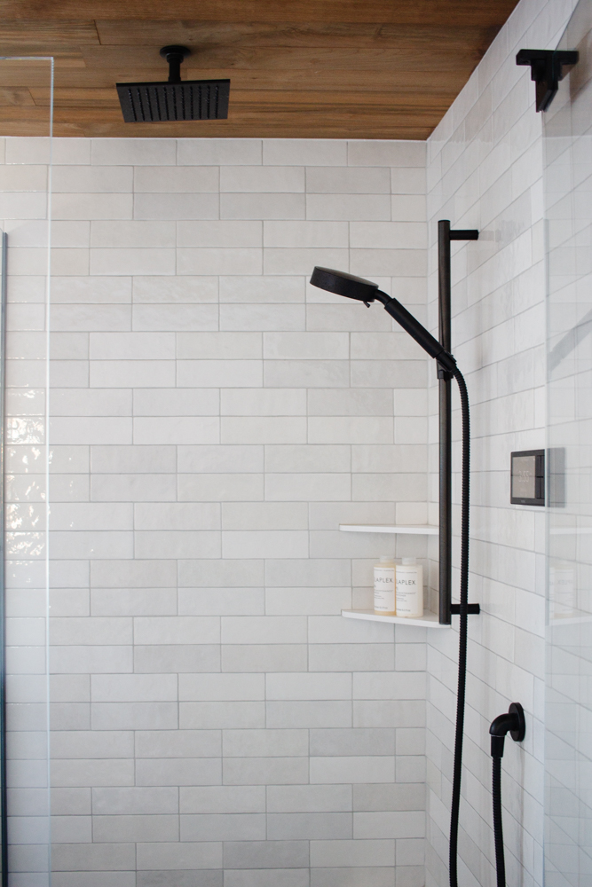 Beautiful white tile, black accents, and a teak ceiling: we love our sexy new shower! Click to see more of our black and white bathroom and shop every source.
