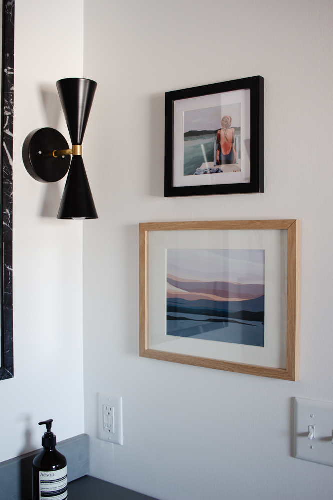 A sweet little art stack brings a hint of color to our black and white primary bathroom. Click to see more and shop every source.