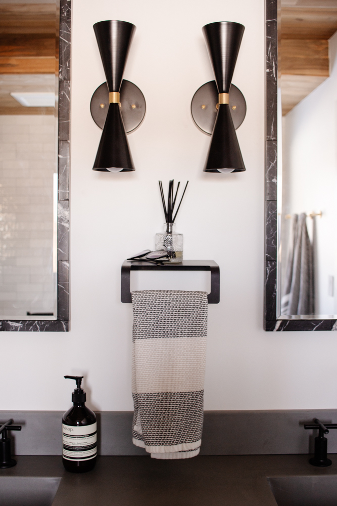 These midcentury modern sconces, black marble mirrors, and hand towel shelf make for such a chic view in our newly completed primary bathroom. Click to see more and shop every source.