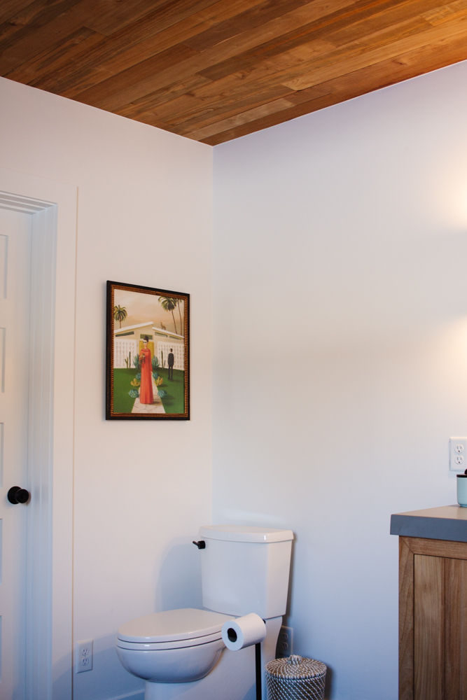 In the corner above the toilet, we have a wonderful print. The secret? It's hiding a shelf that we built in just for toilet paper!